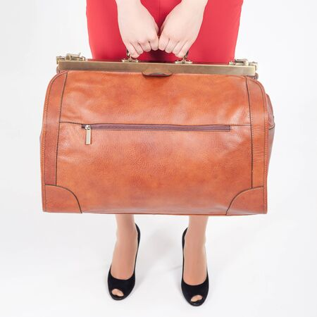allowance: Woman holding luggage. Hand luggage. Lost baggage at airport terminal. Leather suitcase sale. Tourism. Vintage tourist bag. Passenger. Airlines. Weight, baggage dimensions. Allowance. Loss.