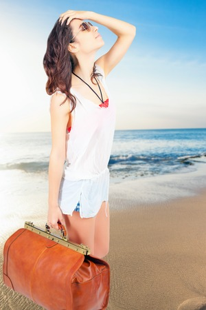 Woman holding hand luggage. Summer travel. Blue sea and sandy beach at Bali. Vacation rentals. Airport. Terminal. Leather suitcase sale. Tourism. Vintage tourist bag. Zdjęcie Seryjne - 53656848