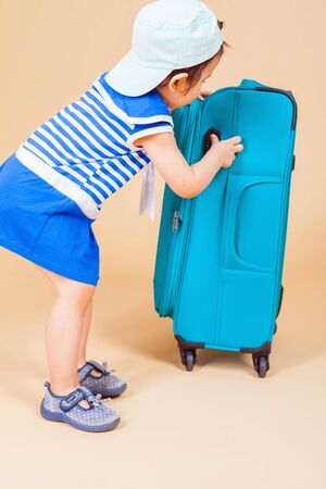 baby stuff: Child packs her things, clothes at luggage, baggage, suitcase. She is going on a journey, vacation. Summer travel Stock Photo
