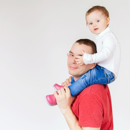 paternal: Happy father holding child at white background. Fashion baby. Looking at camera. Paternal care very important for baby. Custody. Rights Stock Photo