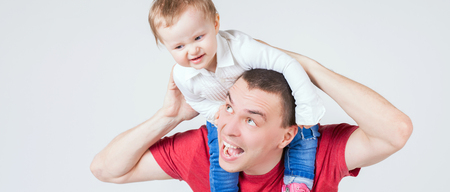 paternal: Happy father holding child at white background. Funny baby. Playing and fly above the head. Paternal care very important for baby.