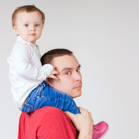 in custody: Happy father holding child at white background. Fashion baby. Looking at camera. Paternal care very important for baby. Custody. Rights Stock Photo