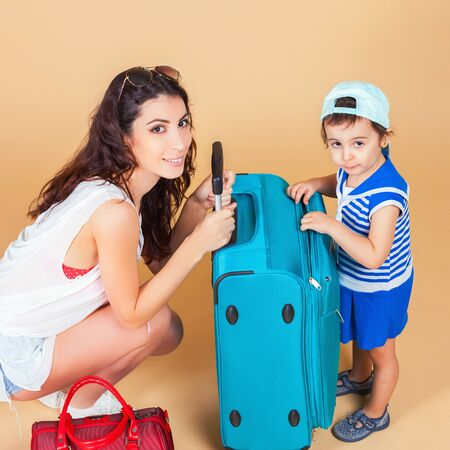 rentals: Child with mother ready travel to Europe, Paris. Family carries luggage at white background. Vacation rentals, packages. Airport terminal. Suitcase. Tourism. Tourist bag. Stock Photo