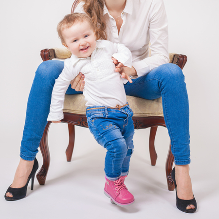 mothercare: Babys first steps. Happy child walking straight at camera. Mother helps and learning her baby. Fashion baby clothes. Jeans. Boots, shoes. Mothercare is most important in baby life