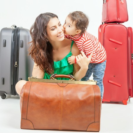 rentals: Child with mother ready travel to Europe, Italy. Travel insurance. Family carries luggage at white background. Vacation rentals, packages. Airport terminal. Suitcase. Tourism. Vintage tourist bag.