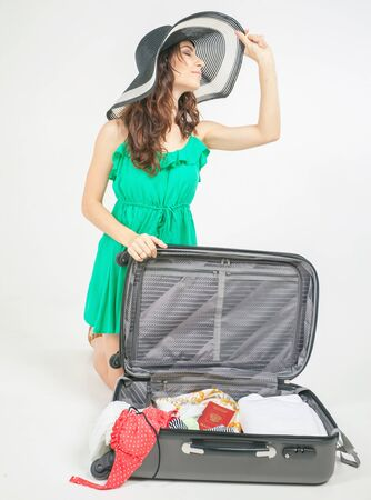 'young things': Young woman packs her things, clothes at luggage, baggage, suitcase. She is going on a journey, vacation. Summer travel Stock Photo