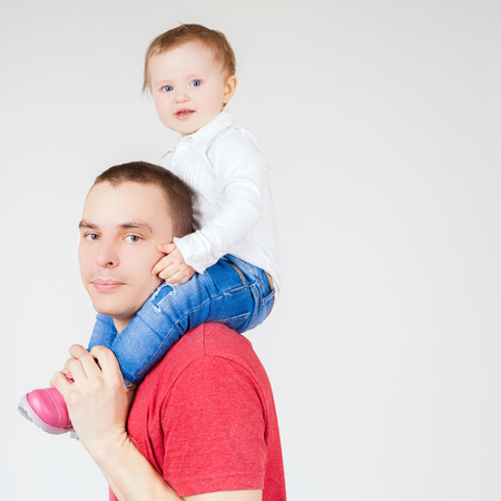 paternal: Funny father holding child at white background. Fashion baby. Looking at camera. Paternal care very important for baby. Custody. Rights