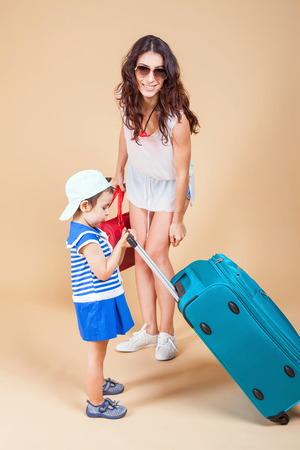 rentals: Child with mother ready travel to Europe, Milan. Family carries luggage at white background. Vacation rentals, packages. Airport terminal. Suitcase. Tourism. Tourist bag.