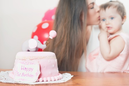 mothercare: Mother with funny baby celebrating first birthday. Cake is surprise for child. Make a first wish. Desire Stock Photo
