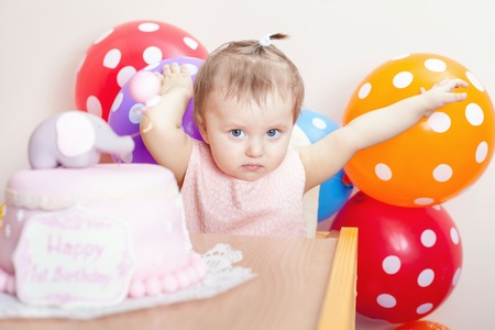 wish desire: Funny baby celebrating first birthday. Cake is surprise for child. Many balloons! Decoration at home. Make a first wish. Desire Stock Photo