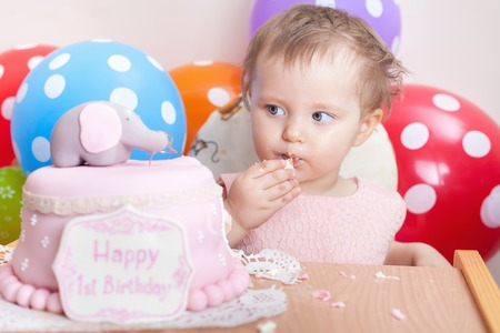 mothercare: Funny baby celebrating first birthday and eating cake. Child with many balloons! Decoration at home. Make a first wish. Desire