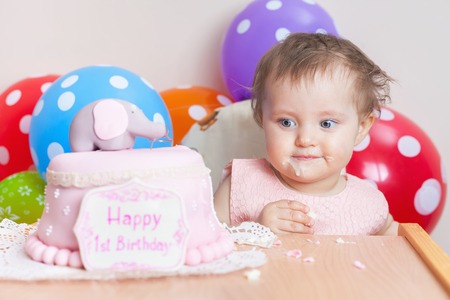 wish desire: Funny baby celebrating first birthday and eating cake. Child with many balloons! Decoration at home. Make a first wish. Desire