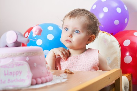Funny baby celebrating first birthday and eating cake. Child with many balloons! Decoration at home. Make a first wish. Desire