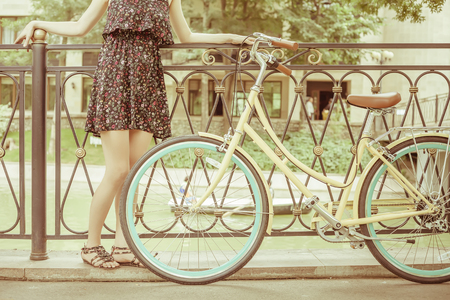 Young girl standing near fence, near vintage city bike at the park. Freedom woman with her happy vacation travel at European city, Paris