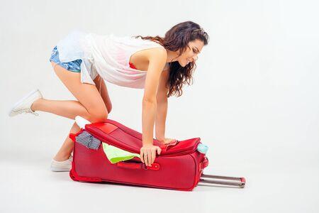Jonge vrouw pakt haar spullen, kleren op volle koffers, bagage, koffer. Journey, vakantie. Zomer reizen. Bagage afmetingen en gewicht. Tourist bag. Passagier. Airlines.
