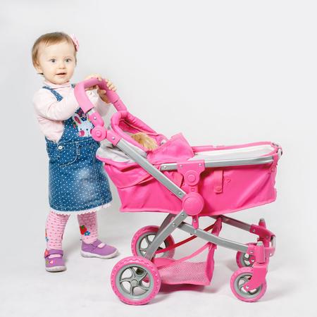 niño empujando: Niña linda que juega con el cochecito de bebé. Cochecito de bebé. tienda del mundo de los niños. Ropa de bebé