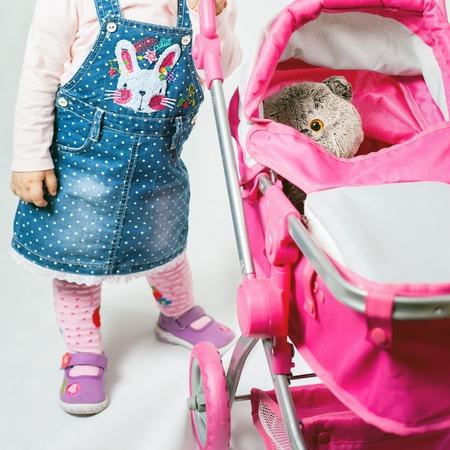 ni�o empujando: Ni�a linda que juega con el juguete del gato y el cochecito de beb�. Cochecito de beb�. tienda del mundo de los ni�os. Ropa de beb�