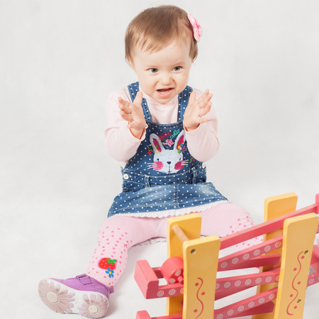 surprised baby: Surprised baby girl playing with toy game for development. Baby clapping. Child. Kindergarten activities. Kindercare learning center. Preschool education