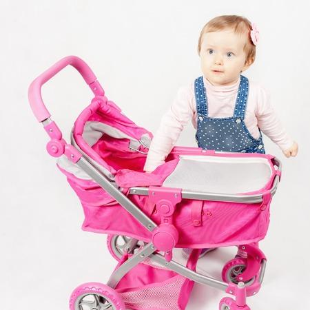 niño empujando: Niña linda que juega con el cochecito de bebé. Cochecito de bebé. tienda del mundo de los niños Foto de archivo