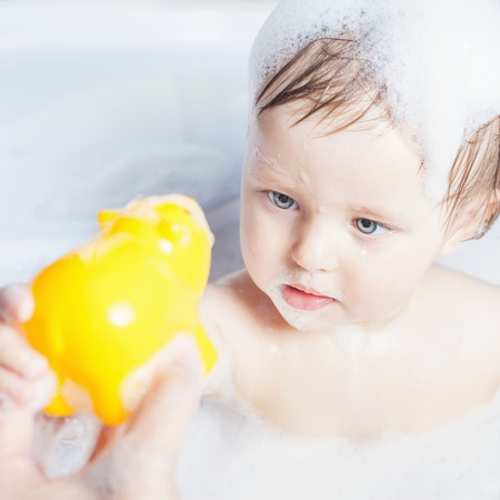 sting: Baby wash in the bath. Playing with water toys. Use soap, shampoo for children. Baby shampoo not sting eyes Stock Photo