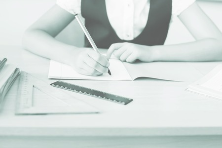 classwork: Desktop background of student sitting at a desk, holding a pen and ready to writing in a notebook for classwork or homework. On table there is a book, a copybook, a ruler, and copy space for text Stock Photo