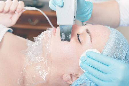 occlusion: Woman in spa salon receive skin treatment. Facial rejuvenation. Ultrasonic cleaning of the face. Creating occlusion for better atomization of the upper layer of the skin. Stock Photo