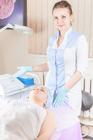 Woman in spa salon receive skin treatment. Facial rejuvenation. Ultrasonic cleaning of the face. Creating occlusion for better atomization of the upper layer of the skin. Фото со стока