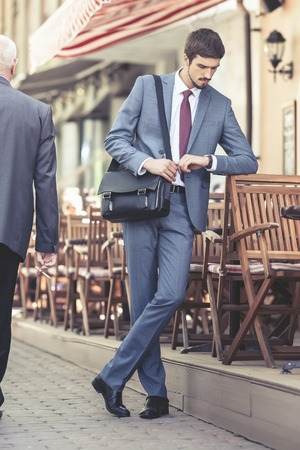 french cafe: Executive businessman walking by street and watching time near french cafe at the early morning. Urban, city life. Breakfast time! Stock Photo