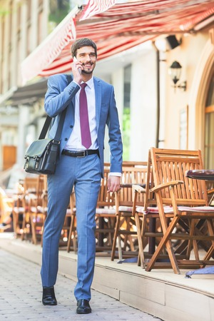 french cafe: Successful businessman talking by mobile phone and walking at street near french cafe. Early morning. Urban, city life. Happy intelligent man.