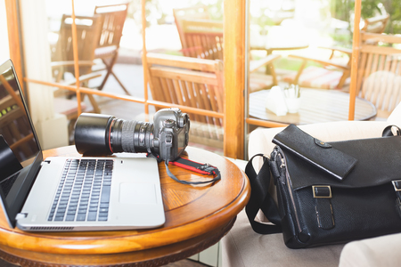 profesional: Laptop computer and dslr camera at cafe. Photographers profesional equipment. There are bag and wallet. Stock Photo