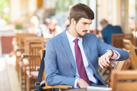 punctuality: Handsome man looking time at watch. Waiting and sitting at sidewalk cafe outdoors. Executive businessman dressed in fashion costume. Stylish man. Punctuality Stock Photo