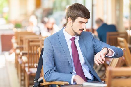 punctuality: Hombre hermoso que mira el reloj de tiempo. Y espera sentado en el caf� de la acera al aire libre. Ejecutivo de negocios vestidos con trajes de moda. Hombre con estilo. Puntualidad Foto de archivo