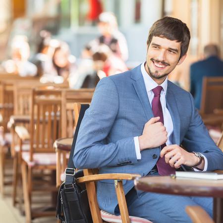 Gut aussehend Mann hat einen französisch Frühstück im Straßencafé im Freien. Smiling Geschäftsmann. Eleganter erfolgreicher Mann. Hat einen Schnurrbart