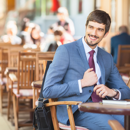 Handsome male has a french breakfast at sidewalk cafe outdoors. Smiling businessman. Elegant successful man. Has a mustache