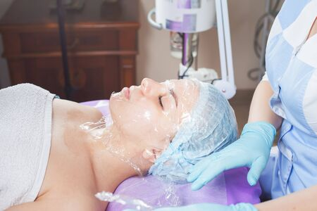 occlusion: Woman in spa salon receive skin treatment. Creating occlusion for better atomization of the upper layer of the skin. Loosening of the skin. Face wrapping