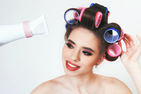 prety: Young girl drying hair by hairdryer. Makeup and hairstyle. Using curlers. Retro, pin up. White background Stock Photo
