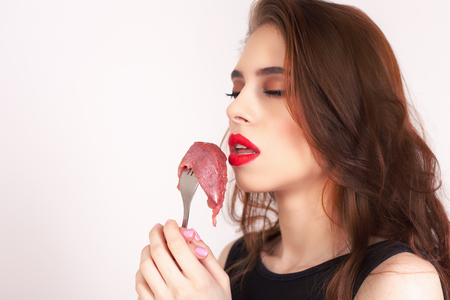 expiration date: Image of woman holding fork with piece of meat at the restaurant. Healthy eating. Meat recipes, expiration date, shelf life