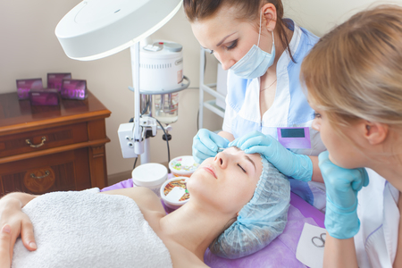 threading hair: Facial rejuvenation procedure. Beautiful woman in spa salon receiving epilation or correction eyebrow using sugar - sugaring. Doctor. Practice for the intern. Stock Photo