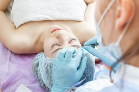 threading: Facial rejuvenation procedure. Beautiful woman in spa salon receiving epilation or correction eyebrow using sugar - sugaring. Doctor. Practice for the intern. Stock Photo
