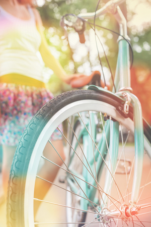activ: closeup of woman standing near blue vintage city bicycle at the city center at sumer. It is like concept for activity and healthy lifestyle and environmentally friendly transport Stock Photo