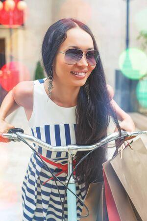 activ: Fashion woman dressed in striped dress with bags and vintage bike has shopping travel to Italy, Milan. Shoping. Wuman has happy vacation travel to Europe Stock Photo