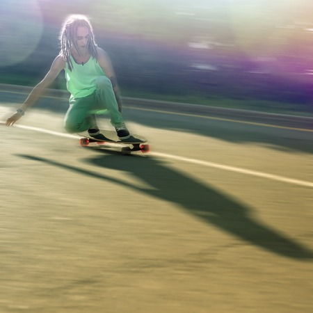 tenager: action image of teenager doing a trick by skateboard by street road outdoors Stock Photo