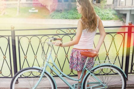 activ: Vintage image of young hipster girl standing near fence near vintage city bike at the park. Sumer. Freedom teenager with her happy vacation travel at European city, Paris Stock Photo