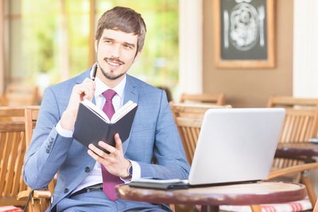 hapy: Hapy businesman has a good idea and holding notebook, siting at cafe outdor, looking at camera. Creativ. Busines plan, flexibility and kpi. Sinking male dressed in blue suit and tie