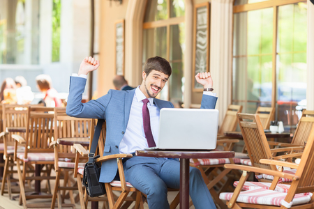 succesful: Succesful man hands up outdor at French cafe, restauran, Paris. Using laptop. Concept of succes deal. Onlin banking.