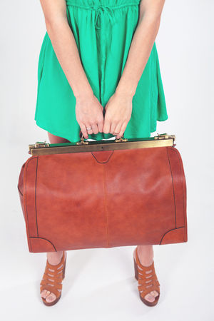 turism: Woman holding hand luggage at the airport terminal. Suitcase sale. Tourism. Vintage tourist bag. Passenger. Airlines. Weight and baggage dimensions. Baggage allowance