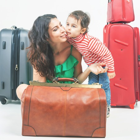 cary: Child with mother ready to trevel. Family caries lugage at background. Airport terminal. Suitcase. Tourism. Tourist bag.