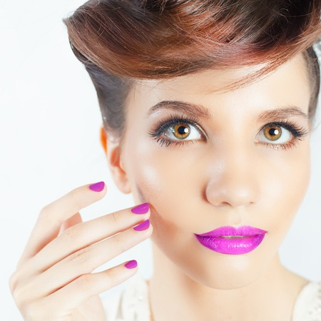 in vouge: Beauty Fashion Female Face with Fancy Hairstyle and Colorful Nail Polish. Perfect skin! Manicure and Fashion Makeup. Glamour Girl. White background