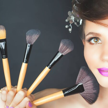 in vouge: Closeup beautiful woman at beauty salon with a fashion make-up and with Fancy Hairstyle. Holding set of professional makeup brushes on a dark background.
