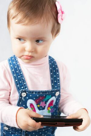funny baby: Funny Baby holding a mobile phone, use the internet or watching cartoons Stock Photo